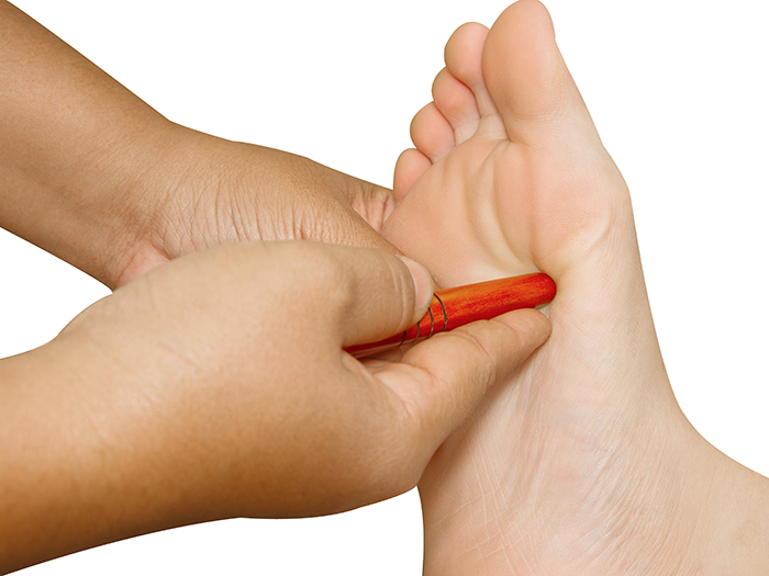 Reflexology foot massage, thai spa foot treatment by wood stick